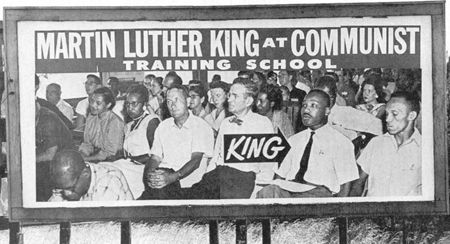 """Billboards showing Dr. King and Rosa Parks attending an integrated event at the Highlander Folk School in 1957 are erected across the South. To the white power structure, integration is a """"Communist plot"""" against the """"Southern way of life."""" Therefore, anyone attending an integrated event is — by definition — a """"Communist."""""""