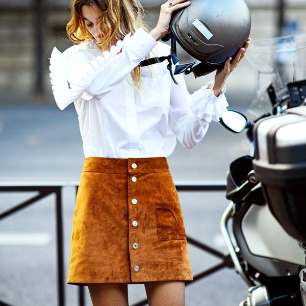 A suede mini skirt gets a dose of polish with a chic white buttoned blouse. This is transitional dressing done well.