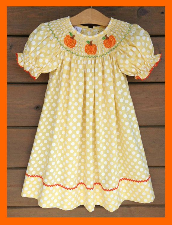 This adorably smocked pumpkin dress in yellow polka dot fabric, trimmed with orange ric rac along its sleeves & hem, is an absolute must