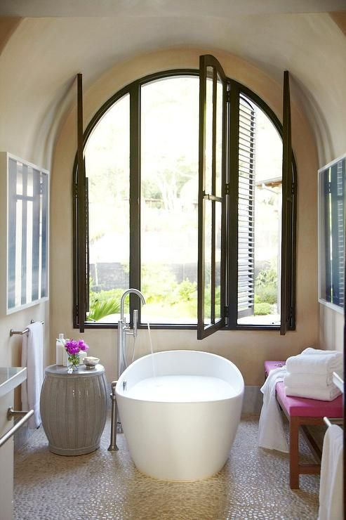 Luxurious bathroom features an arched nook with barrel ceiling filled with a freestanding tub and a floor mount gooseneck tub filler, a gray stool and a pink bench placed under arched windows atop a river rock floor.