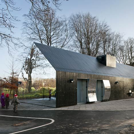 Mirror house in a park in Copenhagen by MLRP. The gabled building is clad with mirrors at both ends and houses spaces for children's activities.