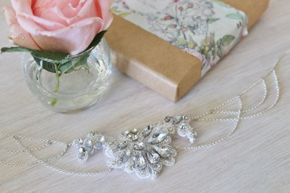 Vintage inspired ivory lace and crystal embellished necklaceThis lovely ivory lace necklace is perfect for the vintage inspired bride. The Czech crystals have all been hand sewn onto the layered lace. A delicate and elegant statement necklace that is timeless and elegant. This necklace features silver lined Czech seed beads and crystals the the vintage bride that wants to make an impact. The cascading rolo chain gives a look of luxury and decadence. This necklace can alo be worn as a…