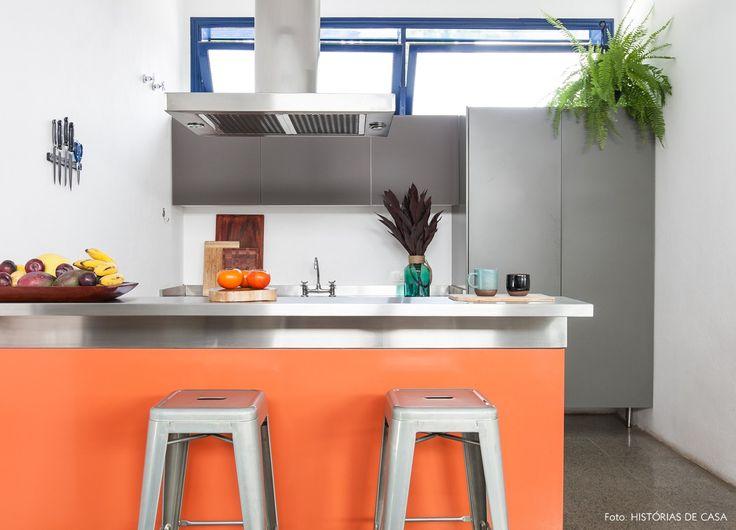 Cozinha decorada com cinza, laranja e muito inox.