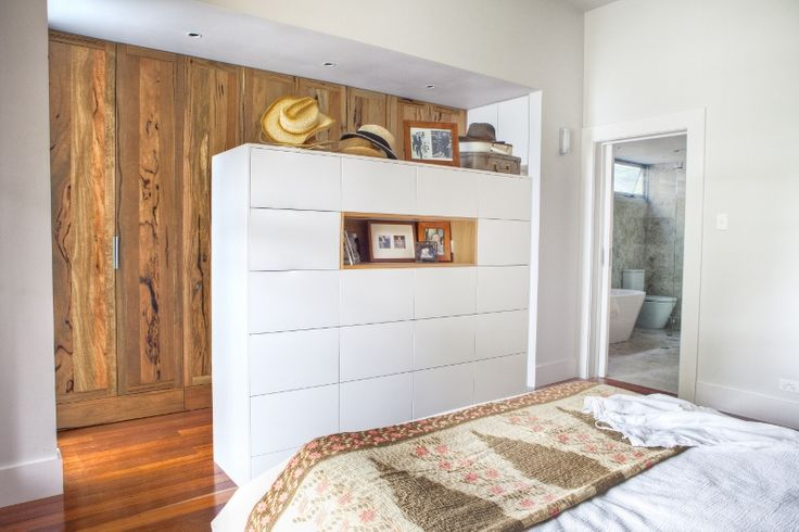 The Salvaged Timber Home by Twinkle & Whistle (for Scoop Magazine) - Bedroom: kantha quilt, pretty cushions, white cabinetry against in-built robes made of salvaged timber - Craig Steere Architects