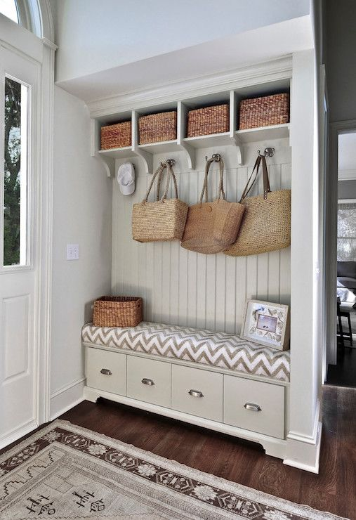 Mudroom off entryway with pale greige built-in storage bench with tongue and groove paneled backsplash topped with open storage cubbies.
