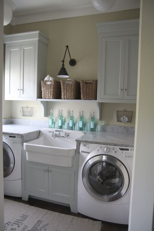laundry room with white marble counters, farmhouse sink, & white shaker cabinets