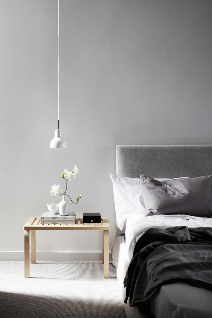 Bedroom: pale grey fabric padded bedhead; white, grey and black bed linen; wooden bench/bedside table; white vase with floral stem; light grey carpet, white minimalist pendant light