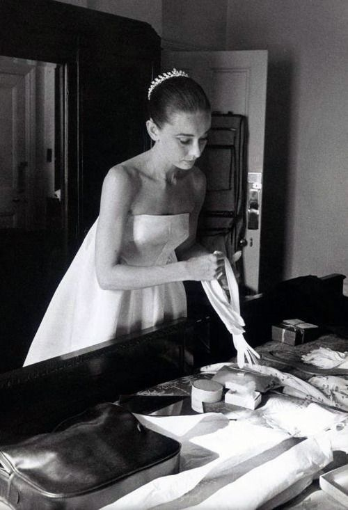Audrey Hepburn, at a dress fitting, chooses a pair of gloves to match her Givenchy gown. Rome, Italy. April 26, 1958.