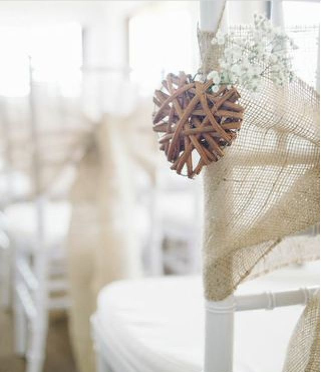 Little wooden hearts on the chairs along the aisle