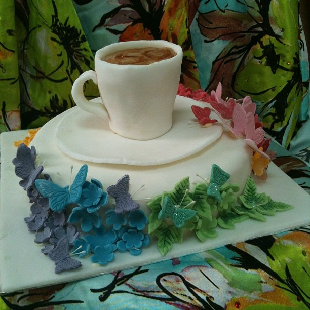 50th Birthday cake, multicoloured butterflies and a coffee cup. Maybe flowers instead of butterflies