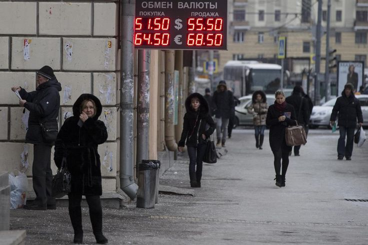 People walk past a display with currency exchange rates in Moscow, Russia, Wednesday, Dec. 3, 2014. The Russian ruble has extended a week of decline, fueled by low oil prices and Western sanctions against Russia over its role in Ukraine's crisis. The top two figures indicate the spread on the dollar-ruble rate and the bottom two figures indicate the the euro-ruble rate. (AP Photo/Pavel Golovkin)