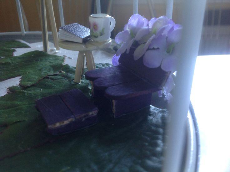 Hyggestol med fodskammel lavet af farvede ispinde. De små borde er lavet af knapper og grillspyd.