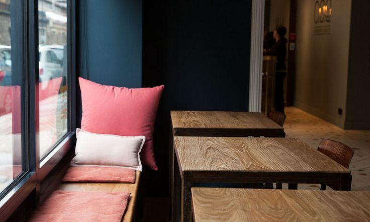 tables en bois et banquettes avec coussins le coq hotel