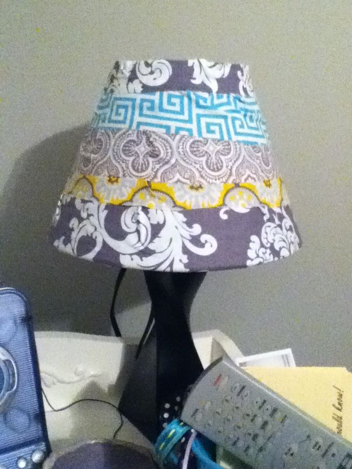 Homemade lamp shade for my sis- take and old lamp shade and hot glue different pieces of fabric onto it