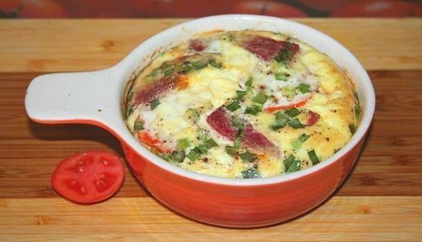 Пышный омлет с помидорами, салями и зелёным луком  - 3 яйца - 170 мл молока - кусочек салями - маленький помидор - зелёный лук - соль, свежемолотая смесь 5-ти перцев - оливковое масло  Миску смазать оливковым маслом, вниз положить кружочки помидора (можно смазать и сливочным маслом).  Потом колбасу и зелёный лук.  Яйца смешать с молоком, посолить и поперчить, сильно взбивать не нужно.  Залить яйцами начинку в миске и отправить в духовку.  Запекать при 200 С примерно 20 минут.