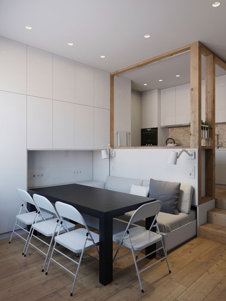 Stored in the living room inlet, a black table and white chairs form a dining space. The pale-coloured couch fits in thematically, offering seating for the other side of the table.