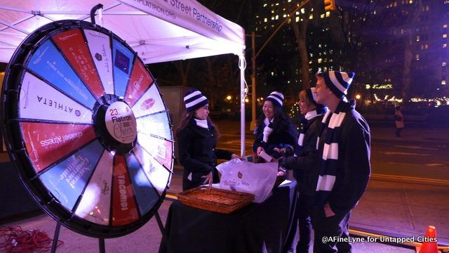 Volunteers from the Flatiron/23rd Street Partnership with the Flatiron Prize Wheel. Buy this Prize Wheel at https://PrizeWheel.com/products/floor-prize-wheels/floor-and-table-prize-wheel-12-24-slot-adaptable/.