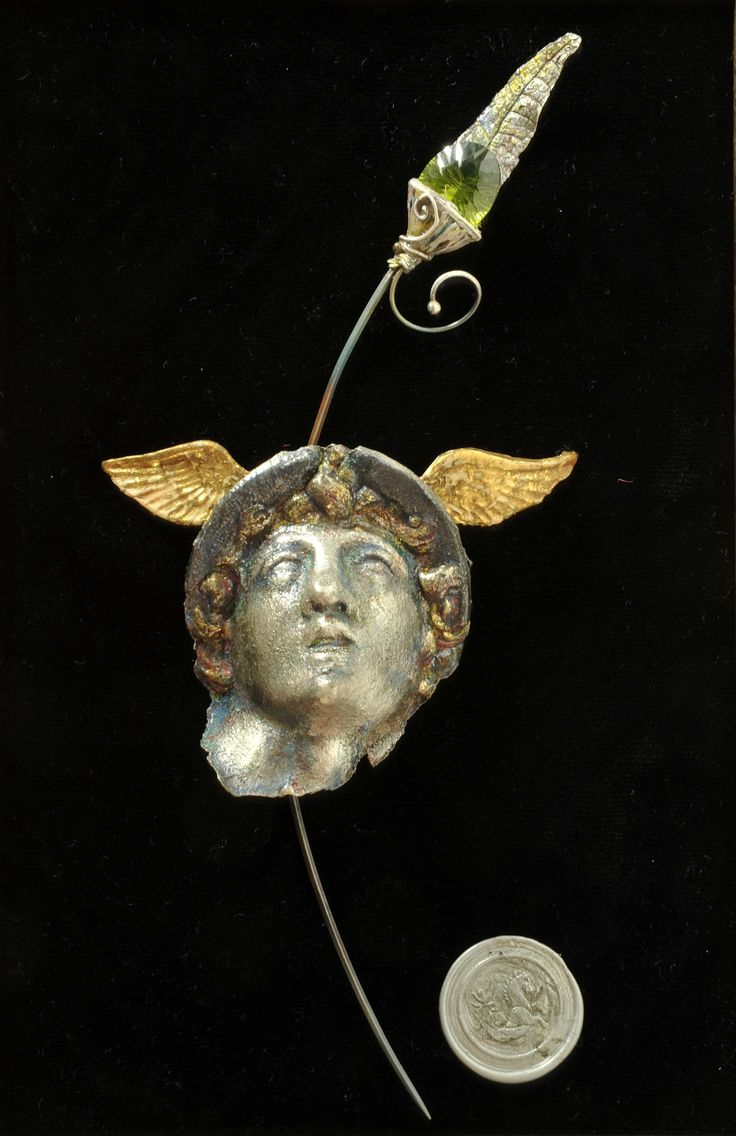 Fine silver clay (Art Clay Silver) Hermes face, sterling silver, peridot, polymer clay and gold leaf wings. Patinated and colour pencil. Removable cloak pin. Mounted in frame with artist's wax seal. Artist: Alan Samons - South Africa. 2008