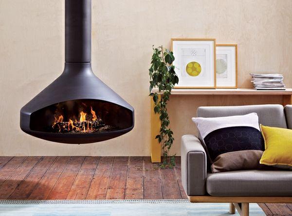 une cheminée suspendue, plancher en bois,sofa gris et coussins décoratifs
