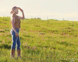 Cowboy girl staring meadow