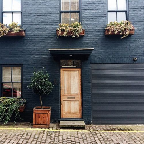 Dark Painted Brick With Stained Wood Door And Planter