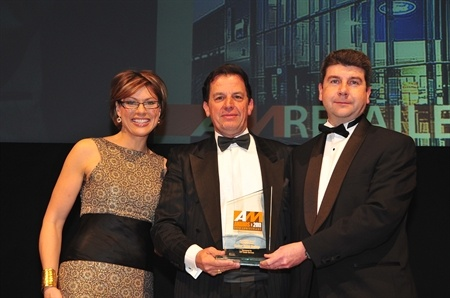 Philip Maskell, Chairman of Essex Auto Group, along with Michael Brown, Assistant Managing Director of Essex Auto Group, receiving the 2011 AM award for Best UK Retail Group from Natasha Kaplinsky.