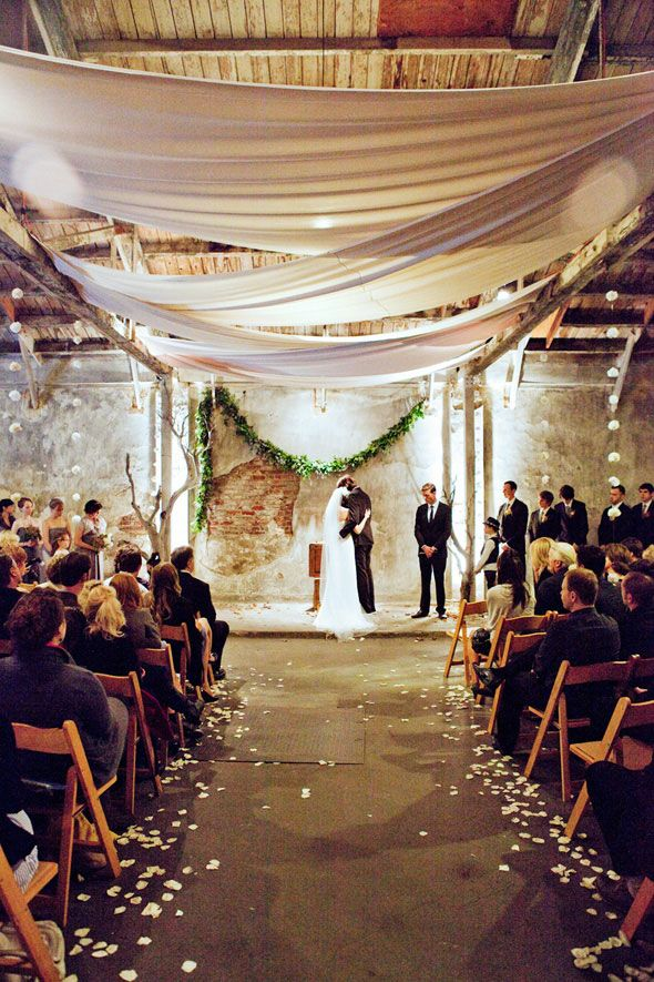 Warehouse wedding, draped fabric, exposed brick, wood... love the textures. Photo: http://llanesweddings.com