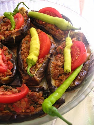 1 lb eggplant, peeled in stripes lengthwise  1/2 ground meat  2 onions, cubed  1/2 bunch parsley, finely choppped  1 tomato, petite diced (for the stuffing)  1 tomato, sliced in half moons (for the top)  green banana peppers, as many as eggplants  ground pepper  salt  2 tbs olive oil  frying oil  1 cup hot water