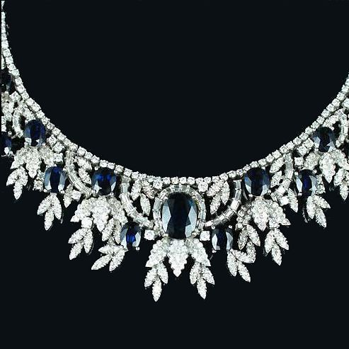 A sapphire and diamond necklace, designed at the front as an articulated bib of stylised foliate motifs set with brilliant, single and baguette-cut diamonds and cushion-shaped sapphires, the largest at the centre.