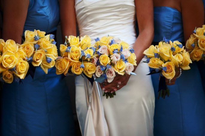 Blue bridesmaid dresses with sunny yellow rose and blue delphinium bridesmaid bouquets. The bride's bouquet is constructed of yellow and blush-ivory roses with touches of delphinium. Photo: Digital Dan Photography #yellow #blue #wedding #flowers #roses #dephinium