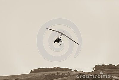 Flying microlight aircraft plane landing approach rural grass airstrip in sepia vintage tone.