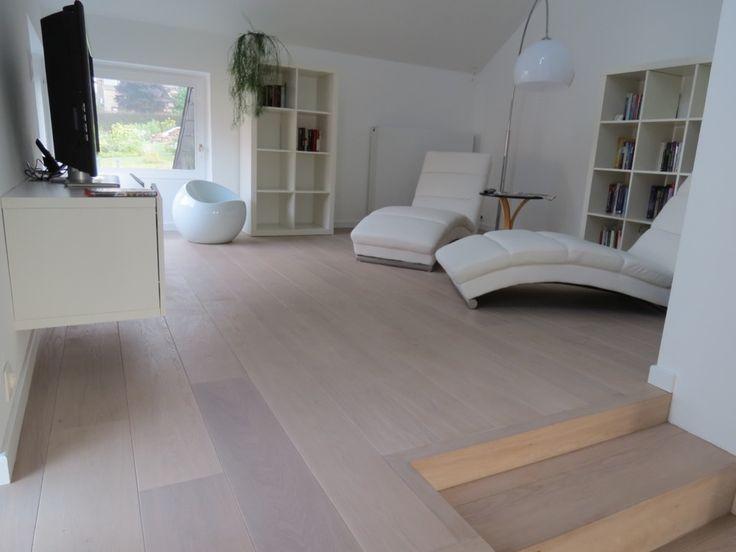 Moderne woonkamer met een strakke houten vloeren in een lichte kleur. Het premium parket heeft kleine kleurverschillen wat voor een warme charme zorgt. De trap werd mooi geintegreed. Een creatie van parketwinkel Fremozia Leuven.