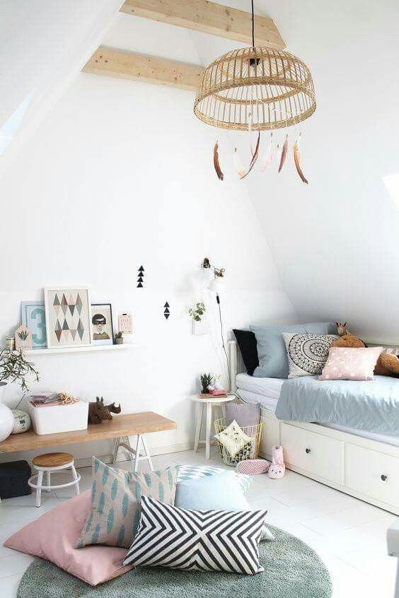 Adorable kids room with white walls, platform bedding, light blue and pink bedding, wicker chandelier with feathers and a small table