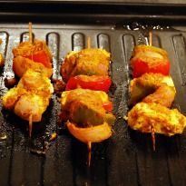 Paneer Tikka Recipe - Every lavish Indian dinner party is sure to have some tikkas. Paneer, capsicum and onions marinated in a yogurt based marinade. Skewered and grilled till brown.