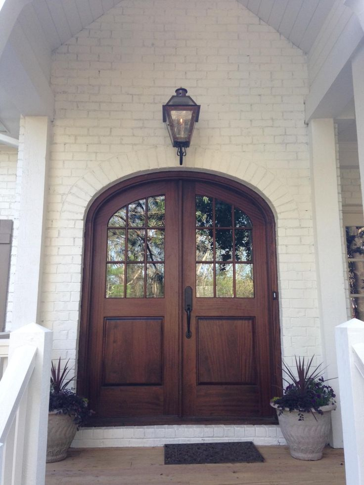 Brown Arched Glass Front Door On White Brick Home Front
