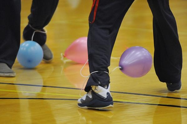 In the game, the students tried to step on each other's balloon while keeping their own balloon from being popped.  Get orange balloons to look like a basketball