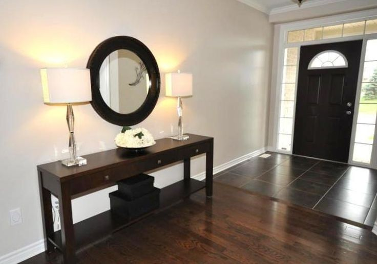 Front door was painted in espresso brown paint to coordinate with the long service table and the stunning round mirror. Bookend crystal lamps make this entrance sparkle!