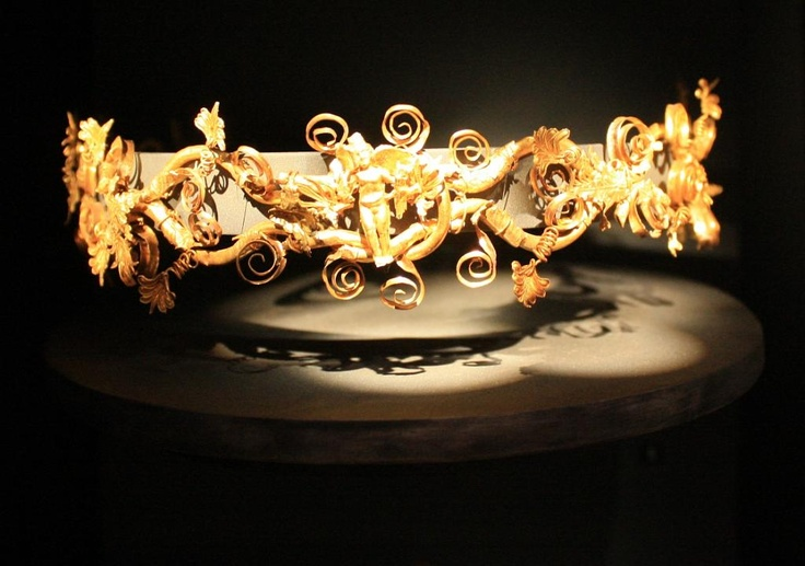 Gold diadem consisting of 8 lyre-shaped sections decorated with acanthus leaves, tendritis and palmettes and a known of Hercules at the center with a winged Eros; 320-330 BC. - Archaelogical Museum of Thessaloniki