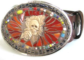 Oval brass belt buckle set with hand carved bone, glass and African trade beads. Attached is a brown leather belt, size small. The buckle measures 3 3/4 inches x 2 3/4 inches. The leather belt can be exchanged for black. Sizes are small, medium or large. American made.