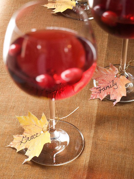 "place cards - Print out our free leaf-shape pattern onto fall-color papers, cut out, and punch a hole at the base of each leaf. Ask guests to pick a leaf and write a word or short phrase describing something they're thankful for, such as ""family"" or ""good health."" Attach leaves to the wineglass stems using lengths of gold cord or raffia."