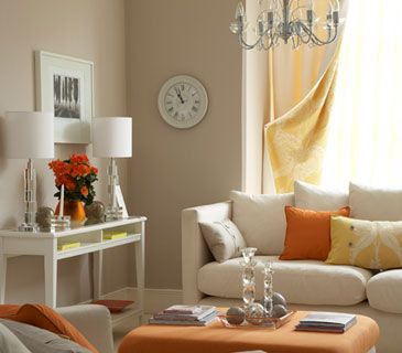 Neutral living room with orange accents. Beautiful.