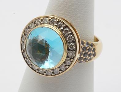 Een 18 krt. geelgouden rozet ring bezet met een grote blauwe topaas en diverse briljanten