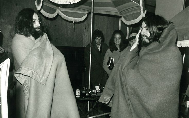 John Lennon and George Harrison swaddled in blankets backstage at Isle of Wight Festival 1969