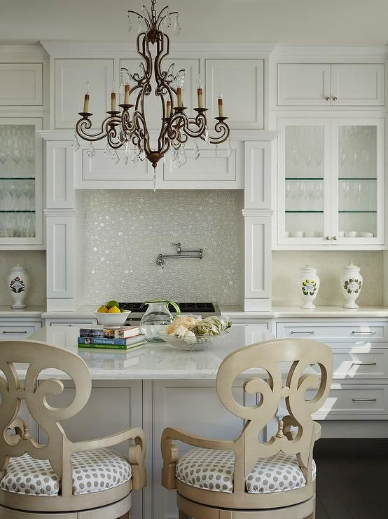 An iron chandelier illuminates a square kitchen island topped with white marble lined with a pair of cream wood scroll counter stools adorned with gray dot seat cushions.