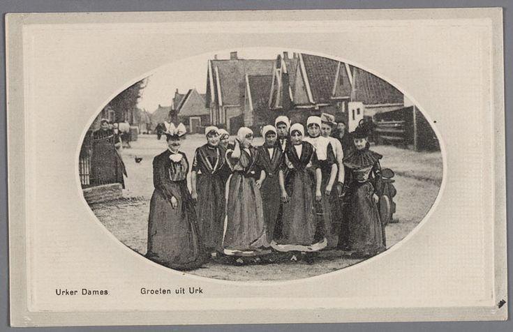Groep jonge vrouwen in klederdracht in een straat, met aan weerszijden dames in modekleding. 1900-1920 #Urk