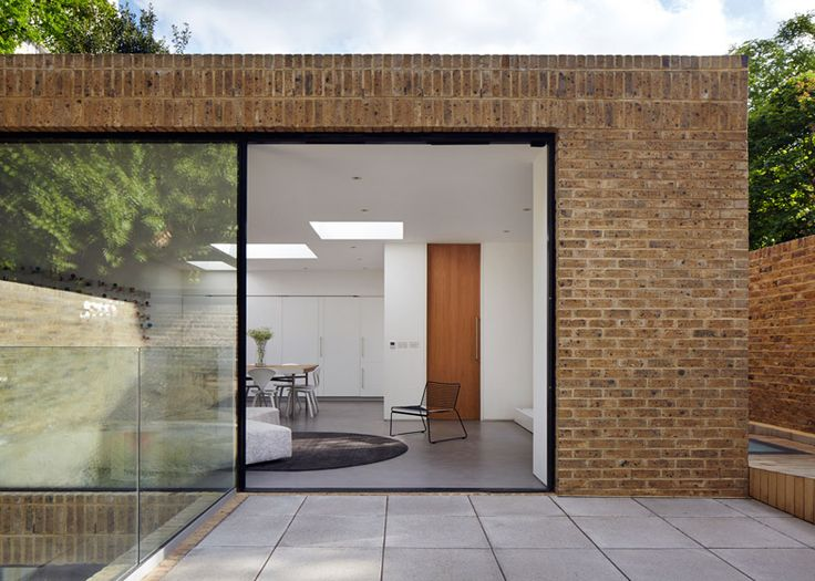 A brick wall conceals the majority of this two-storey house, slotted between a pair of heritage-listed buildings in south London.