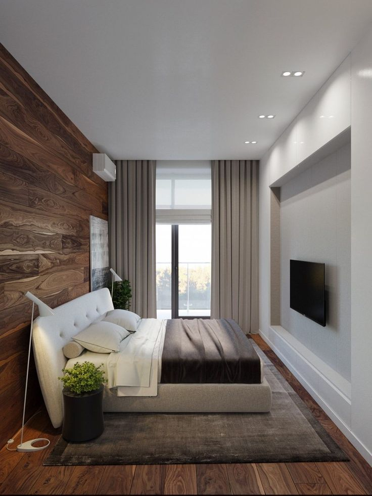 Floor-to-wall wooden panelling in the bedroom creates a cosy aura in the bedroom, made fresh with plant life beside the bed. Here, slim fixtures such as the television, standing lamps and industrial-hued bedding carry on the industrial lodge theme.
