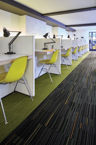 Interface Classic Collection; Green solids and multicolored linear floor patterns fill this classroom / office. The individual desks / workspaces are outlined with the green carpet tile, and accented with matching green chairs. The darker carpet tile has a directional flow with the linear patterns throughout the design. This floor creates an exciting, trendy space for education spaces and public / private offices.