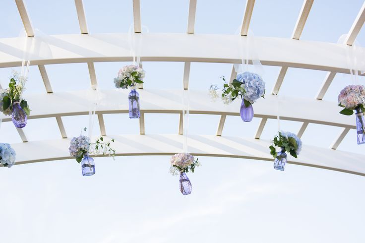 Bud vases hung from our Pergola adds a romantic touch to this outside wedding ceremony! Taken at Running Deer