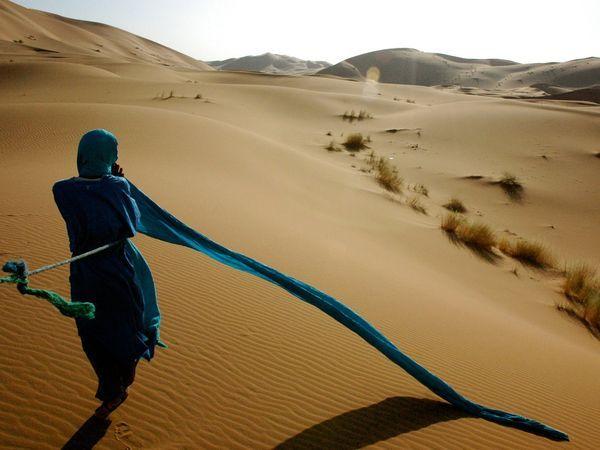 <3  Turbante do homem soprando ao vento de frente para as dunas de areia do deserto do Saara.